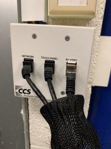 Image of wall plate showing Network, Touch Panel and AV Video cables plugged into the wall plate.